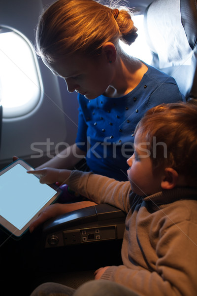 Mother traveling on a plane with her small son Stock photo © d13