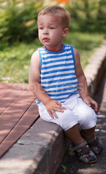 Cute boy sitting on the curb Stock photo © d13