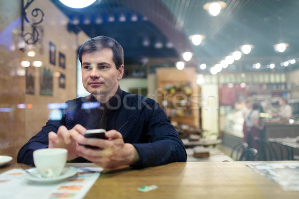 Man at the table texting Stock photo © d13