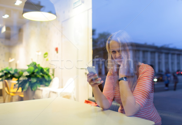 Smiling woman in cafe reading or typing sms Stock photo © d13