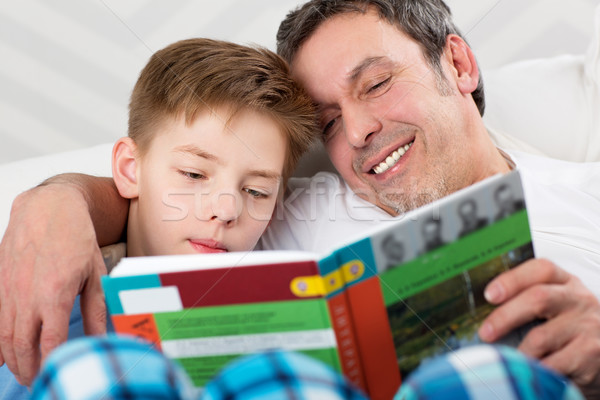 Son and father reading book together Stock photo © d13
