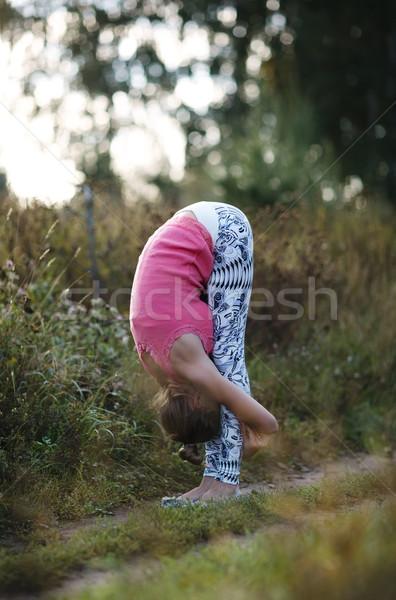 Fiatal nő görbület dupla kezek mögött vidék Stock fotó © d13