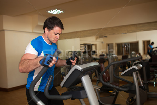 Man exercising on elliptical machine in gym Stock photo © d13