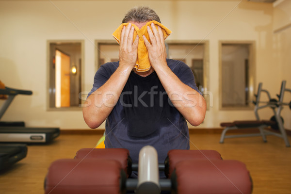 Man wiping face with a towel after training Stock photo © d13