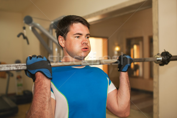 Strong young man exercising with barbell Stock photo © d13