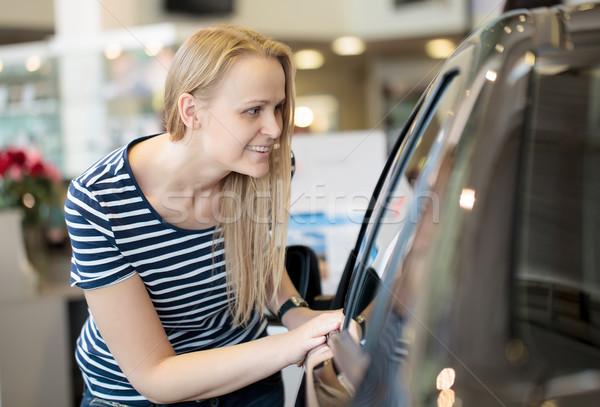 Woman admiring a car at an auto show Stock photo © d13