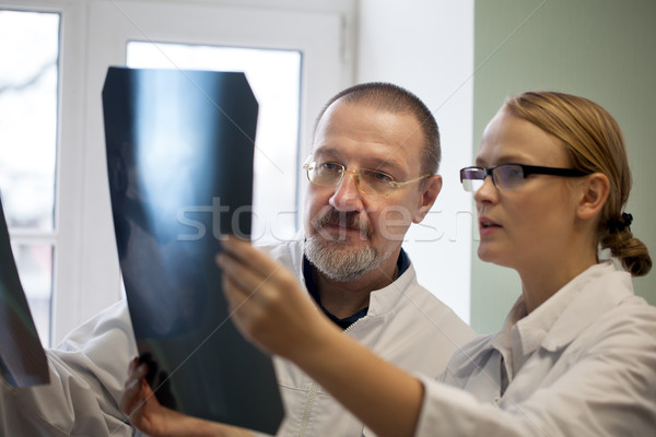 Senior and young doctors examining x-ray images Stock photo © d13