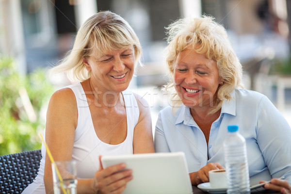 Two women friends using tablet PC in outdoor cafe Stock photo © d13