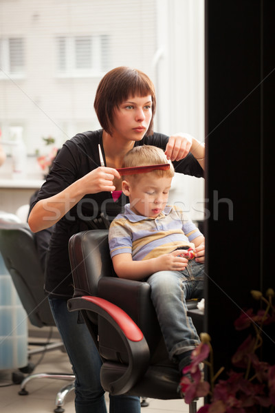 Little boy getting a haircut from hairdresser Stock photo © d13