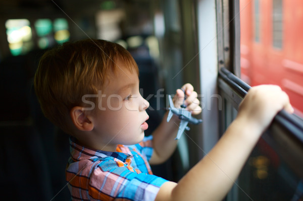 Little boy with toy looking out of train window Stock photo © d13