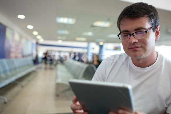 Man reading on tablet PC while waiting at the airport Stock photo © d13