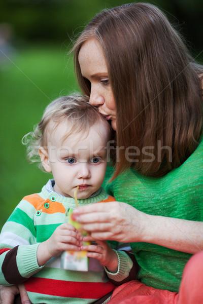 Madre besar nino potable jugo aire libre Foto stock © d13