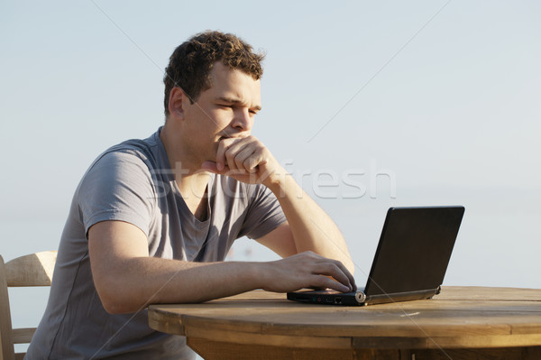 Man typing on a small laptop computer Stock photo © d13