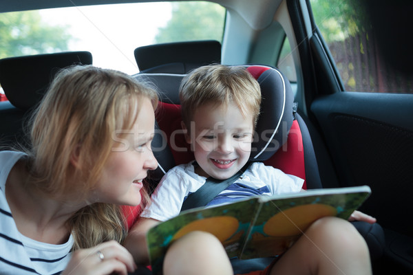 Boy holding book sitting in a car with mother Stock photo © d13