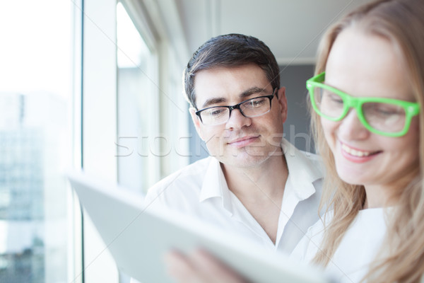 Happy businesspeople working with tablet PC in the office Stock photo © d13