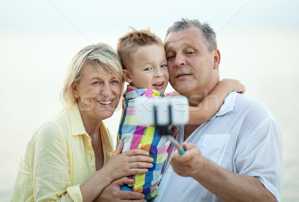 Grandparents and grandson making phone selfie Stock photo © d13