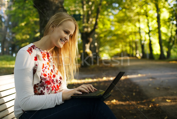 Young woman using her laptop in the park Stock photo © d13