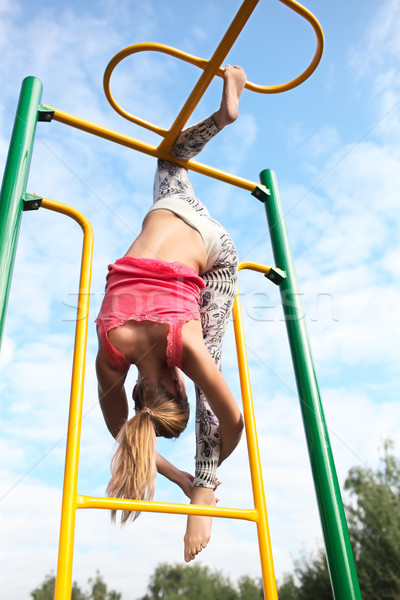 Athletic gymnast working out on metal bars Stock photo © d13