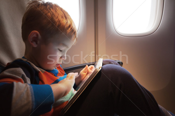 Child using tablet computer during flight Stock photo © d13
