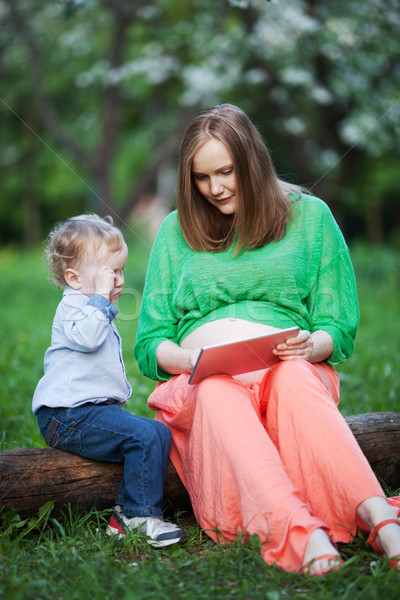 Pregnant mother with little son using touch pad in the park Stock photo © d13