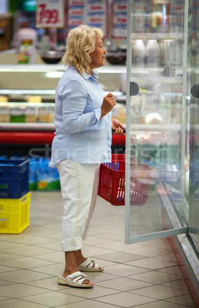 Woman choosing products in open fridge with dairy Stock photo © d13