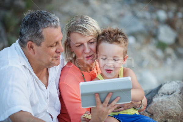 Grandparents and grandson with tablet PC outdoor Stock photo © d13