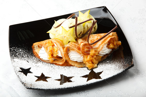 Golden pancakes with carambola and cream Stock photo © d13