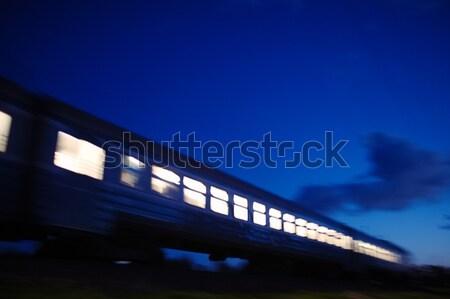 Illuminated train traveling past at night Stock photo © d13