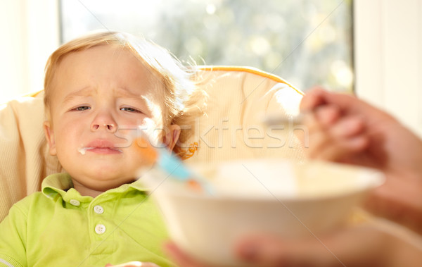 Kid is very disappointmented about porridge. Stock photo © d13