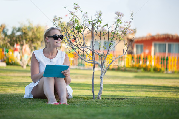 Bella donna seduta a piedi nudi prato indossare occhiali da sole Foto d'archivio © d13