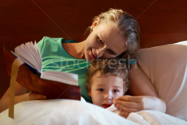 Young mother reading to her child in bed Stock photo © d13
