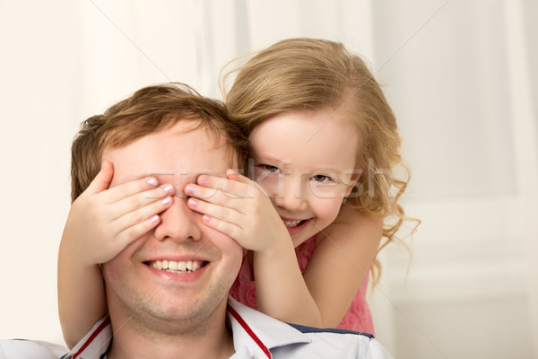 Stock photo: Daughter playing with father closing his eyes