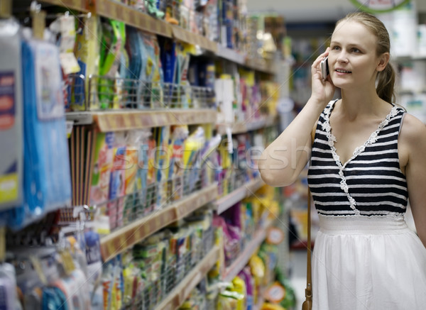 Woman chatting on her mobile while out shopping Stock photo © d13