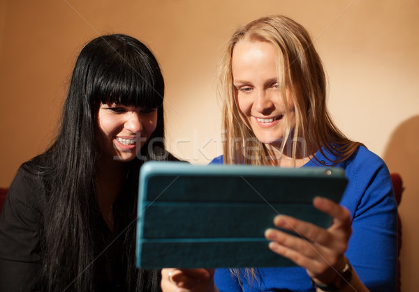 Two young woman reading a tablet-pc Stock photo © d13