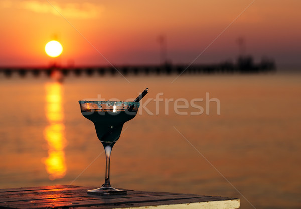 Tropical cocktail overlooking a sunset ocean Stock photo © d13