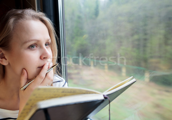 Young woman on a train writing notes Stock photo © d13