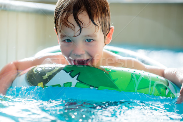 Boy in inflatable ring having fun Stock photo © d13