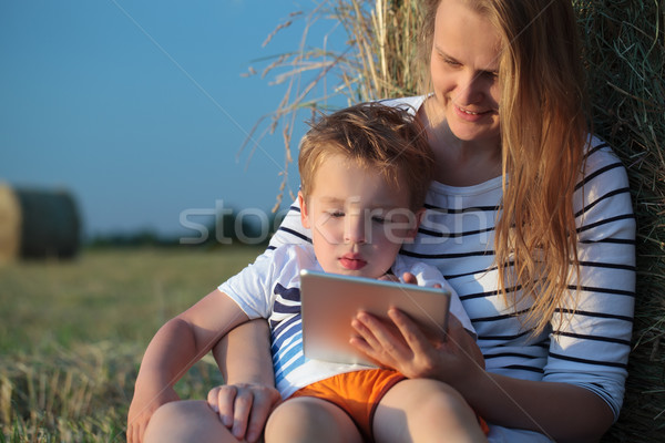 Mother and son with pad sitting by hay roll in the field Stock photo © d13