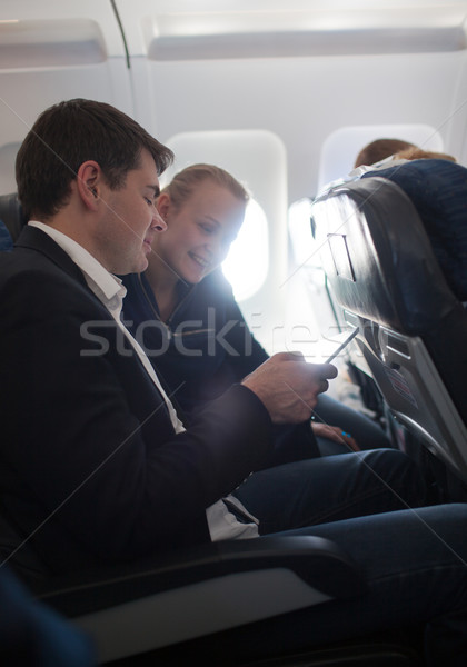 Young man and woman using cell phone in plane Stock photo © d13