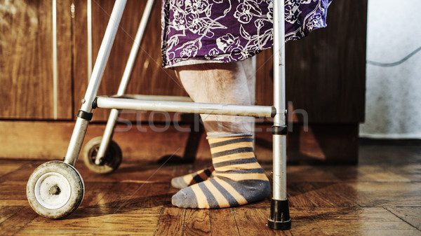 Elderly woman going slowly with the help of walker Stock photo © d13