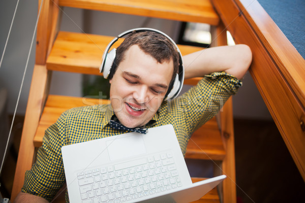 Man entertaining with laptop and music at home  Stock photo © d13