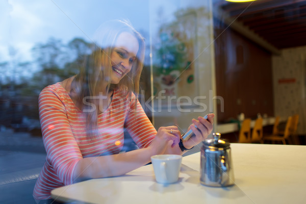 Young woman using a mobile phone in cafeteria Stock photo © d13