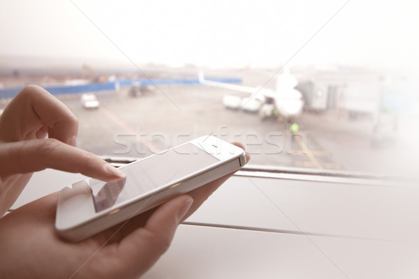 Woman using smart phone by the window at aiport Stock photo © d13
