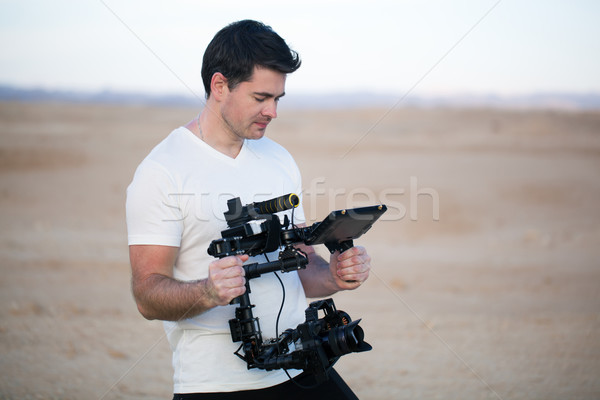 Young man using steadycam for shooting on beach Stock photo © d13