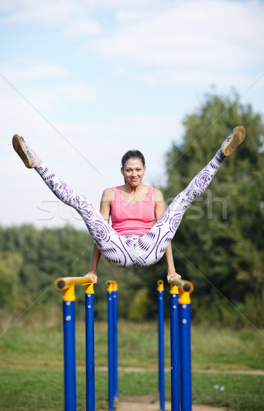 Athletic gymnast exercising on parallel bars Stock photo © d13