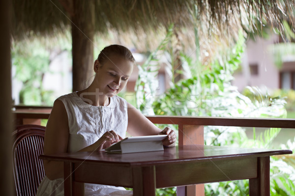 Smiling woman using tablet computer in cafe during vacation Stock photo © d13