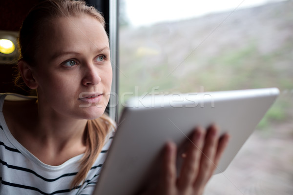 Woman traveling on a train with tablet Stock photo © d13
