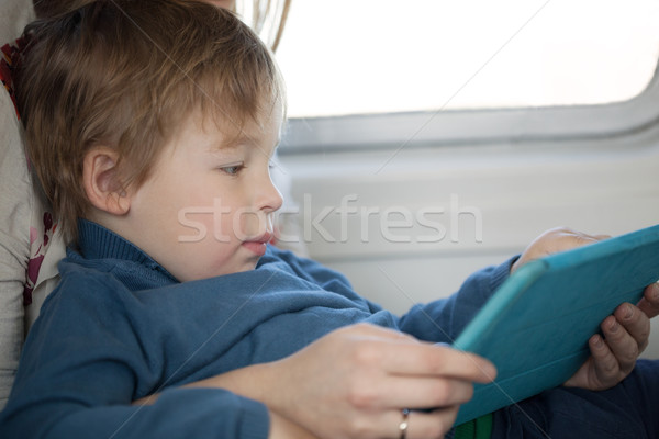 Small boy looking at a tablet in an airplane Stock photo © d13