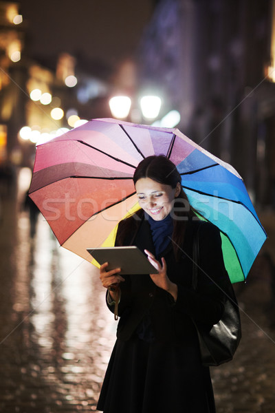 Brunette woman using tablet on the street on rainy day Stock photo © d13