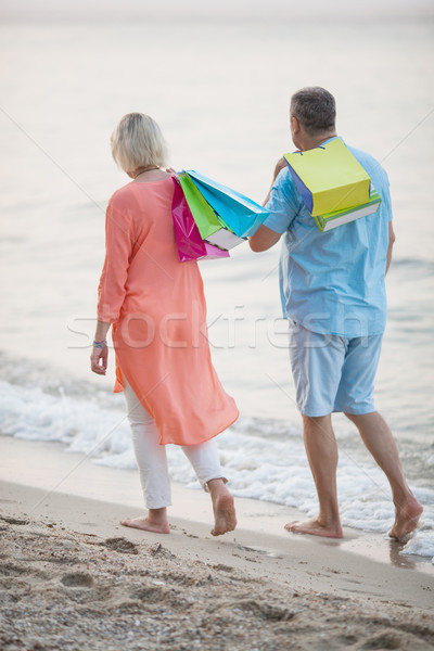 Couple walking on the beach after vacation shopping Stock photo © d13